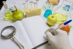 Inspektören för matsäkerhet testar frukt från marknaden Anteckningsbok med forskningrapporten och blå penna på labbtabellen med arkivfoto