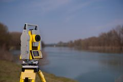 Inspektörutrustning på en tripod nära floden arkivbild