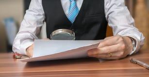 Inspektion des Dokuments mit Lupe Schicht analysiert Vertrag stockbild