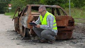 Inspektor, der nahe gebrannt hinunter Autowrack auf der Seite der Straße überprüft und schreibt stock footage