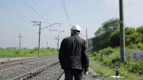 Inspektor des Bahnverkehrs reizbar sprechend auf Funksprechgerät Bahnarbeitskraft im weißen Sturzhelm, der Pläne hält, planen stock video