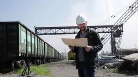 Inspektor des Bahnverkehrs reizbar sprechend auf Funksprechgerät Bahnarbeitskraft im weißen Sturzhelm, der Pläne hält, planen stock footage