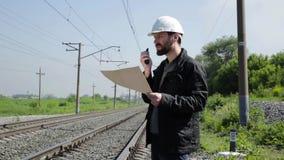 Inspektor des Bahnverkehrs reizbar sprechend auf Funksprechgerät Bahnarbeitskraft im weißen Sturzhelm, der Pläne hält, planen stock video footage