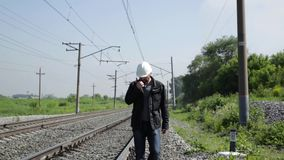 Inspektor des Bahnverkehrs reizbar sprechend auf Funksprechgerät Bahnarbeitskraft im weißen Sturzhelm gehend entlang stock video