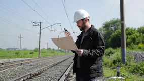 Inspektor des Bahnverkehrs sprechend auf Funksprechgerät Bahnarbeitskraft im weißen Sturzhelm, der Pläne hält, planen stock footage