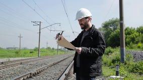 Inspektor des Bahnverkehrs sprechend auf Funksprechgerät Bahnarbeitskraft im weißen Sturzhelm, der Pläne hält, planen stock video footage