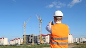 Inspektor in einem weißen Sturzhelm und in einer Warnungsjacke fotografiert den Bau eines Apartmenthauses stock video