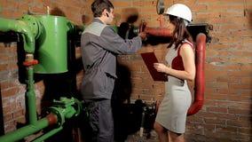 Inspektor i pracownik sprawdzamy ogrzewanie Pracownik mierzy tubki temperaturę z laserowym pirometrem zbiory wideo