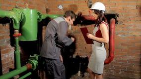 Inspektor i pracownik sprawdzamy ogrzewanie Pracownik mierzy tubki temperaturę z laserowym pirometrem zdjęcie wideo