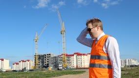 Inspektorchef in den schwarzen Gläsern auf dem Hintergrund des Baus des Hauses entfernt den weißen Sturzhelm von stock footage