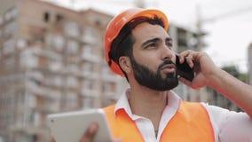 Inspektorgebäude-Aufsichtskraftingenieur, der auf Smartphone spricht und an der Tablette steht auf der Baustelle arbeitet stock footage