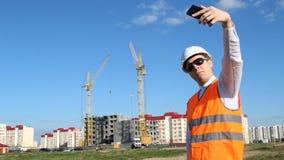 Inspektorleiter tut selfie auf dem Hintergrund des Bauens eines Hauses stock video footage