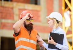 Inspektorski i brodaty brutalny budowniczy dyskutuje budowa postęp Projekta budowlanego sprawdzać Budowa obrazy stock