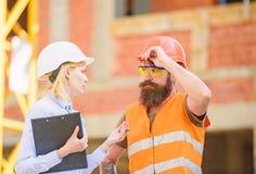 Inspektorski i brodaty brutalny budowniczy dyskutuje budowa post?p Projekta budowlanego sprawdza? Budowa zdjęcia royalty free