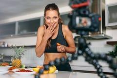 Inspelninginnehåll för ung kvinna för hennes blogg i kök arkivfoto