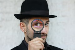Inspetor concentrado engraçado no chapéu negro, no revestimento e nas luvas olhando através da lente de aumento sobre o fundo bra Fotografia de Stock