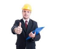 Inspetor da construção com o capacete de segurança e a prancheta do terno que mostram l Foto de Stock Royalty Free