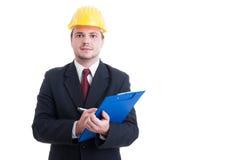 Inspetor da construção com terno e capacete de segurança que guarda a prancheta Fotos de Stock Royalty Free