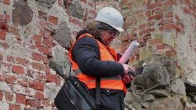 Inspetor de construção que verifica o tijolo em ruínas velhas video estoque