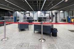 Inspetores vazios em uma máquina prévia do raio X e do varredor do controlo de segurança ao embarque no aeroporto internacional imagens de stock royalty free