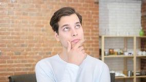 Inspiração de espera Homem novo pensativo que guarda a mão no queixo, olhando afastado Fotografia de Stock