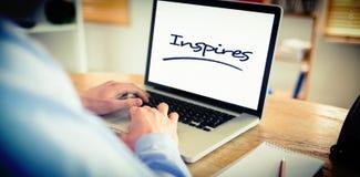Inspira contra o homem de negócios que trabalha em seu portátil Fotos de Stock