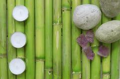 Inspiracyjna scena z trzy świeczkami wyrównywać, kamieniami i gemstones na naturalnym zielonym bambusowym tle, obrazy royalty free