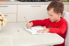 Inspirado por el muchacho dibuja una imagen en el papel en la tabla foto de archivo