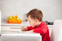 Inspirado por el muchacho dibuja una imagen en el papel en la tabla imágenes de archivo libres de regalías
