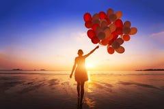Inspiratie, vreugde en gelukconcept, silhouet van vrouw met vele vliegende ballons stock afbeelding