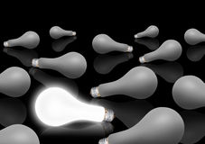 Inspiration. A field of light bulbs with one glowing Royalty Free Stock Image