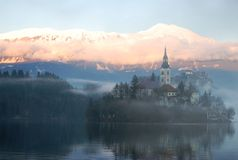 Inspiration. The Bled island church reflecting in the water with the snowy mountains and the Bled castle in the background Royalty Free Stock Photos