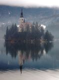 Inspiration. The Bled island church reflecting in the water in the misty afternoon Stock Photography