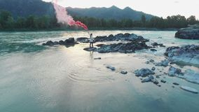 Aerial view hiker woman with smoke bomb in hand. Inspiration aerial view from quadcopter. Woman standing on the coastline, enjoying victory and freedom holding stock video footage