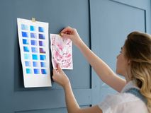 Inspiration art workspace decor drawing swatch. Inspiration art painting. painter workspace decor. woman sticking drawing and color swatch palette to the blue Stock Photo