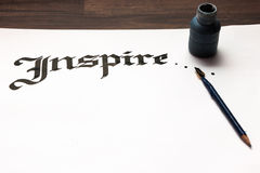 Inspiration calligraphy lettering background. Word drawn with inks on paper sheet . Drawing lessons, art school, creativity concept stock photos