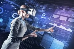 Positive young specialist smiling in virtual reality and looking happy. Inspiration. Cheerful young programmer smiling and pointing in front of herself while Royalty Free Stock Images