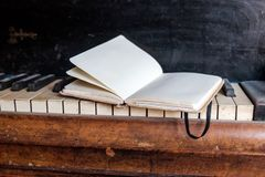 Inspiration composes music. Opened notebook on old dirty piano keys - close up Stock Photo