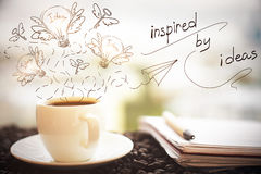 Inspiration concept. Close up of coffee cup, notepad with pen and creative sketch on blurry city background. Inspiration concept stock photography