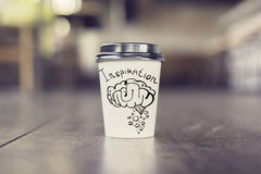 Inspiration concept. Takeaway coffee cup with brain sketch on wooden floor. Inspiration concept Stock Image