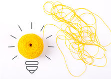 Inspiration concept. Yarn yellow light bulb metaphor for good idea. Symbol of idea as light bulb on sheet of paper from skein of thread, isolated on white Royalty Free Stock Photo