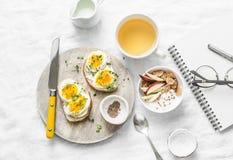Inspiration för morgonfrukosttabell - smörgåsar med gräddost och det kokta ägget, yoghurt med äpplet och linfrö, växt- detox royaltyfri foto