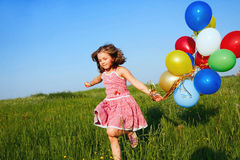 Inspiration. Happy little girl jumping outdoors with balloons Royalty Free Stock Images