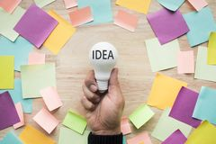 Inspiration ideas concepts with hand holding white lightbulb. And colorful notepaper on wood table.nobody Stock Photo