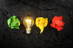 Inspiration. Lit lightbulb with crumpled paper balls, idea or inspiration concept Stock Image