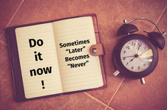 Inspiration quote : Do it now ! Sometimes later becomes never. On notebook and clock on the floor Stock Image