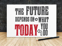 Inspiration quote :. `The future depend on what you do today` on white frame in black brick wall and wooden flooring ,Motivational typographic royalty free stock image