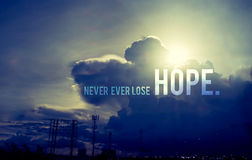 Inspiration quote :. ` Never ever lose hope` with sun burst behind cloud,Motivational typographic Royalty Free Stock Image