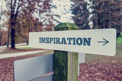 Inspiration signboard on a wooden post with a right pointing arr stock photography