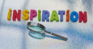 Inspiration. Text 'inspiration' in colorful uppercase letters with hand held magnifier alongside to indicate author or writer looking for inspiration, reflective Stock Photo